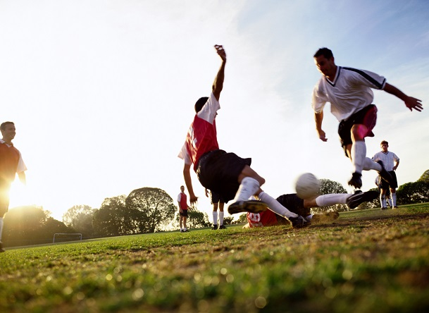 Fussballer grätscht den Ball